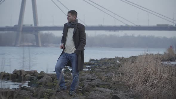 Thumbnail for Portrait of Stressed Caucasian Man Throwing Away Rock and Walking Along Riverbank. Upset Young Guy