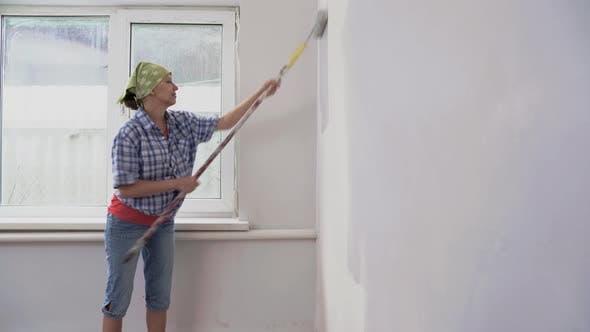 Frau Maler malt Wand drinnen durch Paint Roller und Paint.