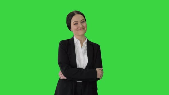 Confident Young Businesswoman Posing with Crossed Arms on a Green Screen, Chroma Key.