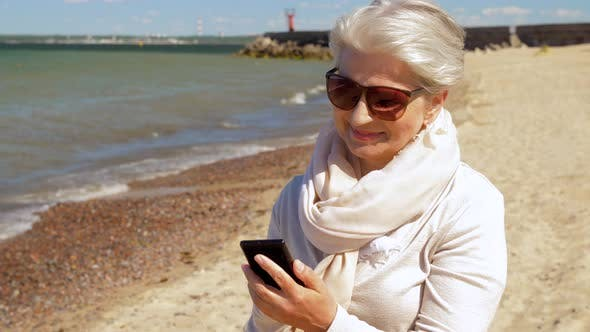 Thumbnail for Senior Woman Using Smartphone on Summer Beach