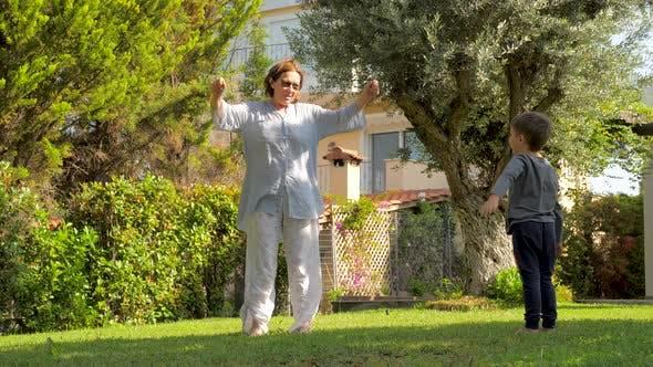 Thumbnail for Fröhliche Großmutter Spaß mit Enkel Outdoor. Kleiner Junge mit Spaß