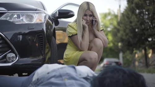 Portrait of Crying Beautiful Woman Sitting at Corpse of Lady Hit By Car, and Talking on the Phone
