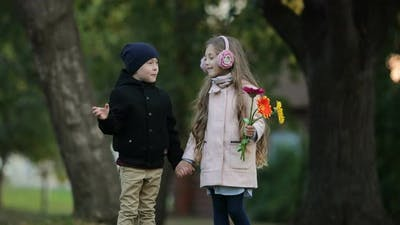 Two Children Stand and Laugh in the Park