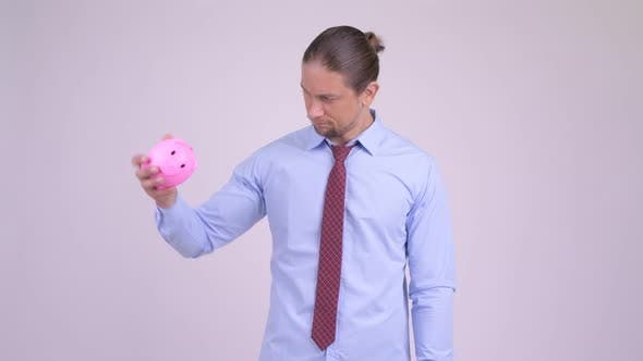 Thumbnail for Stressed Businessman Holding Piggy Bank and Giving Thumbs Down
