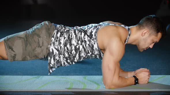 Cover Image for Attractive Sportsman Doing Plank Pose Cardio Workouts on Floor Fitness Mat in Gym