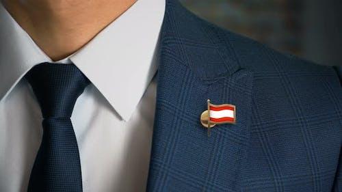 Homme d'affaires marchant vers la caméra avec drapeau du pays broche Autriche