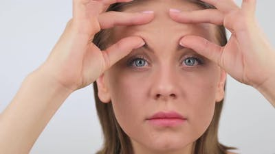 Portrait of Young Woman Displeased with Wrinkles on Her Forehead