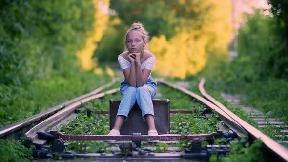 Thumbnail for Beautiful Girl Tourist Sitting on Suitcase on Railway in Summer Forest. Waiting Tourist Woman