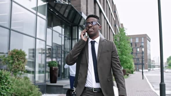 Thumbnail for African Businessman Walking and Talking on Phone