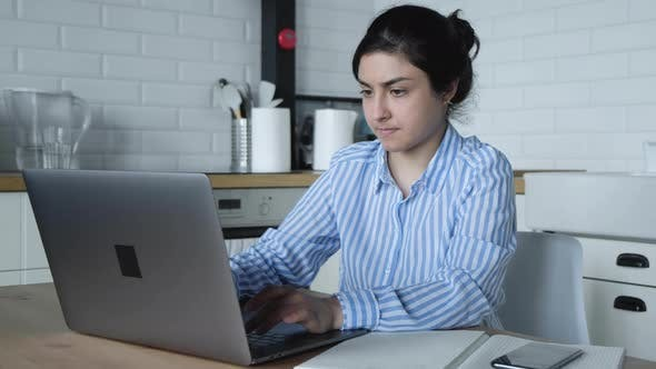 Thumbnail for Konzentrierte tausendjährige indische Frau, die zu Hause am Computer arbeitet