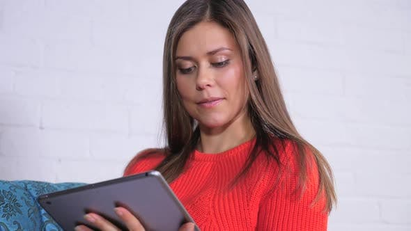Thumbnail for Attractive Young Female Playing On Her Tablet 2 1