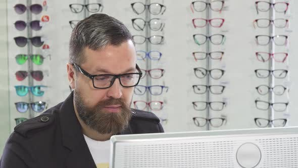 Thumbnail for Mature Optometrist Working on a Computer at His Store