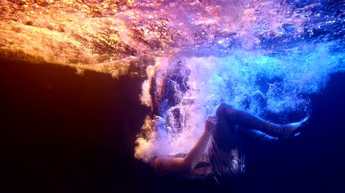 Woman in a Silver Dress with Long Red Hair Falls Under the Water As If Into Another Dimension