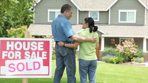 Thumbnail for Couple look at new home, SOLD sign in foreground