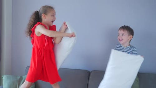 Happy Family Young Baby Sister and Little Kid Brother Enjoy Funny Pillow Fight on Bed, Brother and