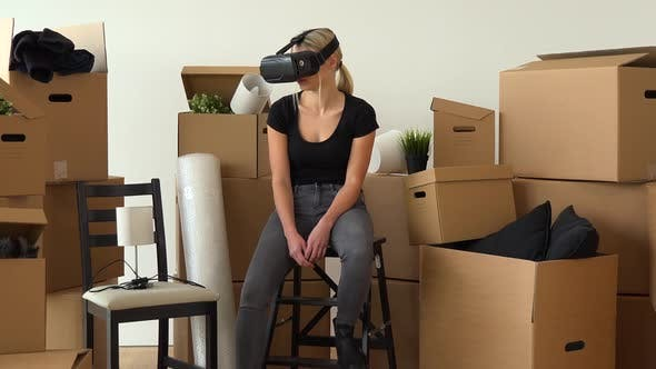 Thumbnail for A Moving Woman Sits on a Chair in an Empty Apartment and Uses VR Headset, Surrounded By Boxes