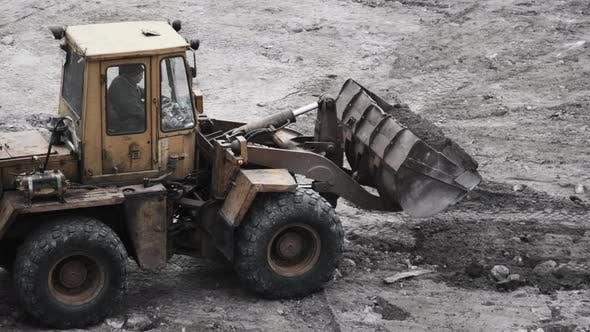 Thumbnail for An Old Bulldozer on Rubber Wheels Works on Construction Site.