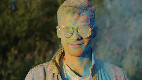 Slow Motion Portrait of Excited Guy Smiling While Friends Throwing Powder Paint at Him Having Fun at