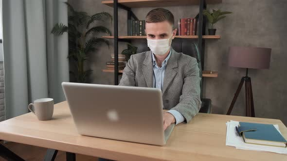 Confident Young Man in Face Mask Office Workplace. Remote Chatting Colleague Internet Online Meeting