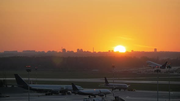 Cover Image for Airport View at Golden Sunset with an Airplane Taking Off