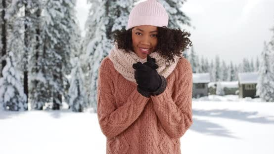 Thumbnail for Cute African American female in cozy sweater in snowy forest, laughing joyfully