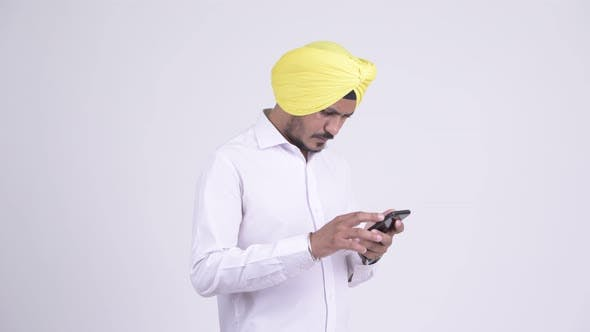 Thumbnail for Bearded Indian Sikh Businessman Using Phone and Looking Shocked