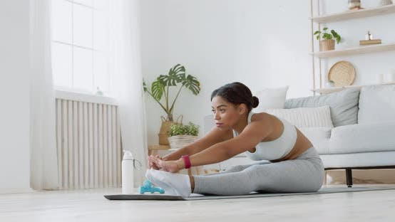 Flexibility Training, Young Black Lady Stretching at Home, Sitting on Floor and Reaching To Feet
