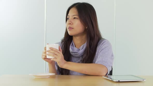 Thumbnail for Young woman at desk with coffee