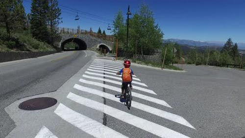 A boy rides his mountain bike across a crosswalk.