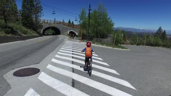 Thumbnail for A boy rides his mountain bike across a crosswalk.