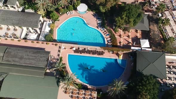 Thumbnail for Aerial drone shot of hotel gardens and swimming pools at a sunny resort.