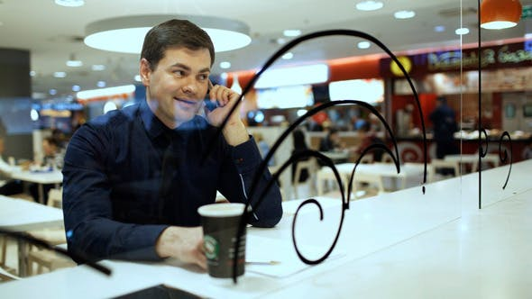 Thumbnail for Businessman Having A Phone Talk In Cafe