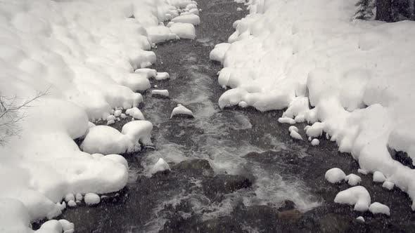 Thumbnail for Schnee fällt über einen schneegesäumten Fluss
