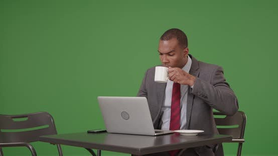 Thumbnail for A black businessman works on his laptop while sipping coffee on green screen