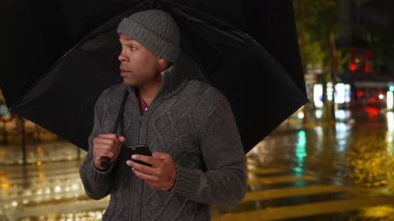 Thumbnail for African male holding umbrella outside on rainy night in the city