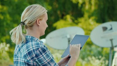 Side View of Woman Sets Up a Satellite Dish, Uses a Tablet