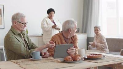 Senior Men Showing Tablet to Women