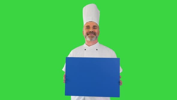 Smiling Male Chef Cook Holding Blank Board on a Green Screen Chroma Key