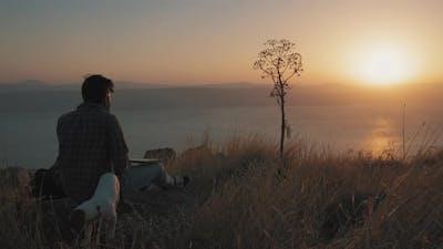 A man opens a computer at sunset