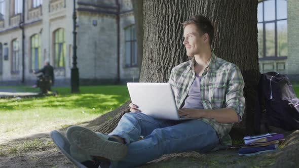 Cover Image for Senior Student Working on His Project on Laptop Sitting Under Wide Tree, Campus