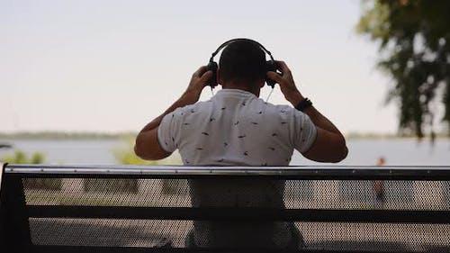 Man Puts on Big Headphones Sitting on Bench