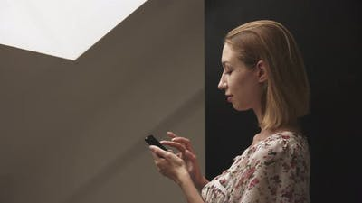 Young Woman in Profile Works on Smartphone