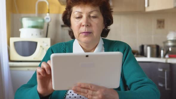 Thumbnail for Portrait Of A Mature Woman Is Using A White Tablet Pc At Home