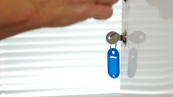 Female Hand Using Key with Blue Keyholder To Close Metal Door in White Shelf. Hand Closes Steel Cell
