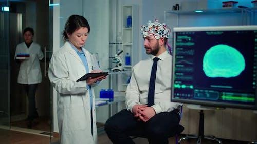 Specialist Doctor in Neuroscience Taking Notes on Clipboard