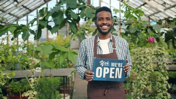 Business Owner Holding Open Sign Standing in Greenhouse Smiling Welcoming People