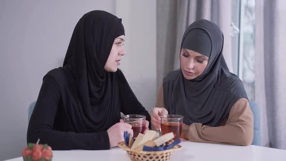 Thumbnail for Two Thoughtful Muslim Women Sitting at the Table and Talking