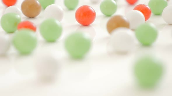 Thumbnail for Lot of various color bonbons on the white shiny and reflective background 4K 3840X2160 UHD video - M