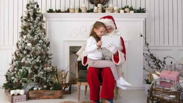 Thumbnail for Little Girl Sitting with Serious Santa Claus Using Tablet