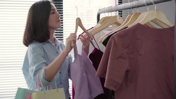 Asian woman shopping clothes. Shopper looking at clothing on the rail indoors in clothing store.